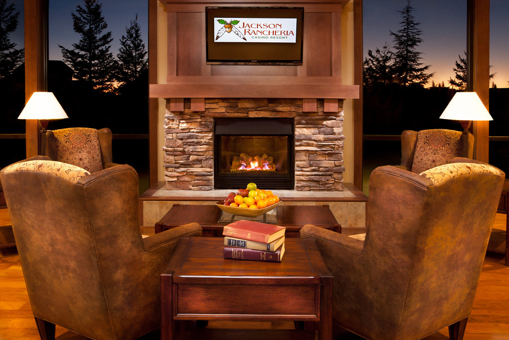 Hotel lobby with leather chairs at fireplace and sunset