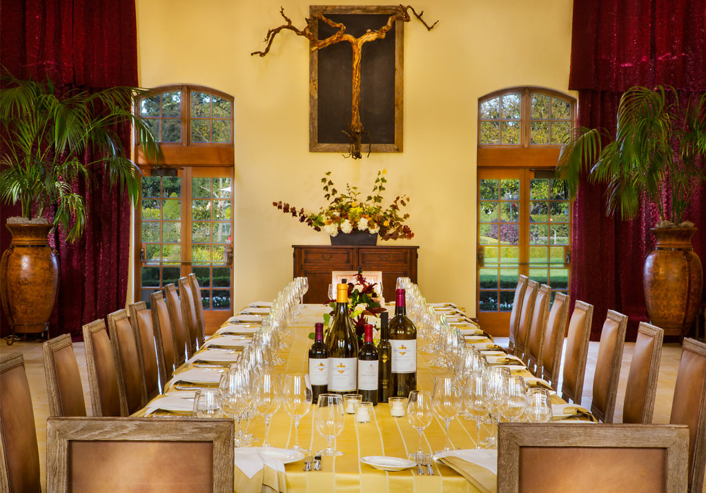 Dining room with long table set with wine and crystal
