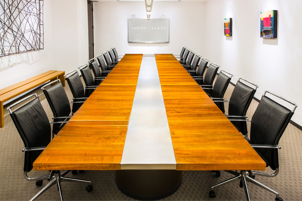 Law firm meeting room with long wooden table and black leather chairs