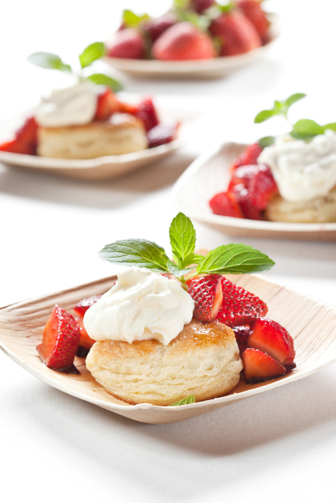 Eclair topped with whipped cream and strawberries on white plate and linen