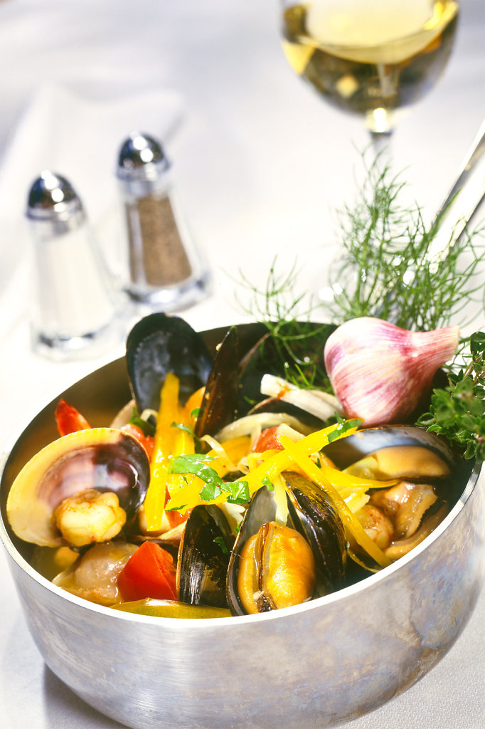 Sea Food with Vegetables in pot with thyme and anise on white linen with glass of wine