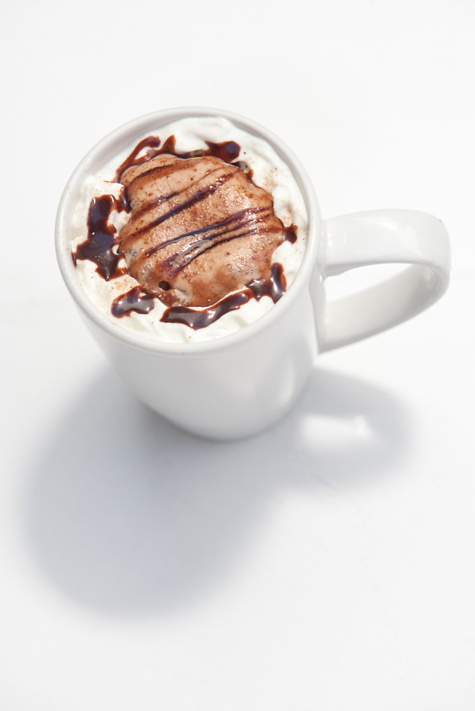 Hot chocolate in a white mug on white table