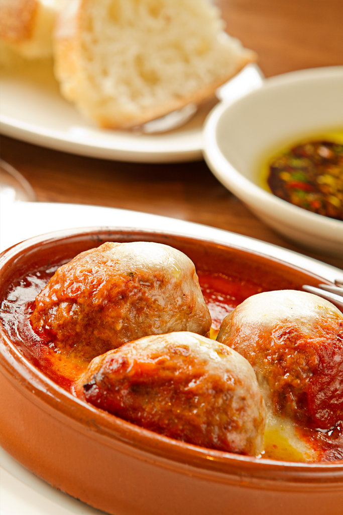Succulent meatballs in red sauce in clay pot with chese