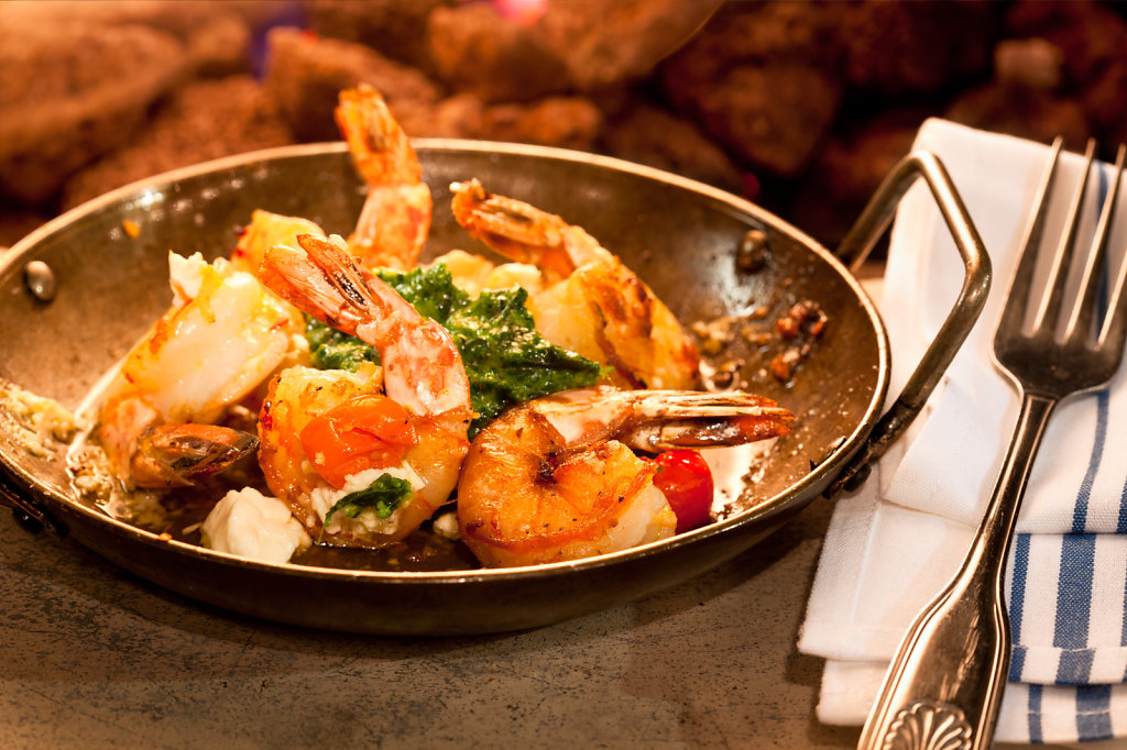Sauteed scampi in pan served on stone