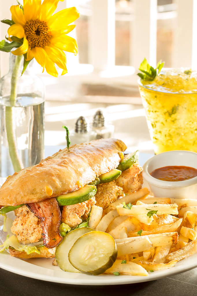 Chicken sandwish with avocado and fries on white dining table
