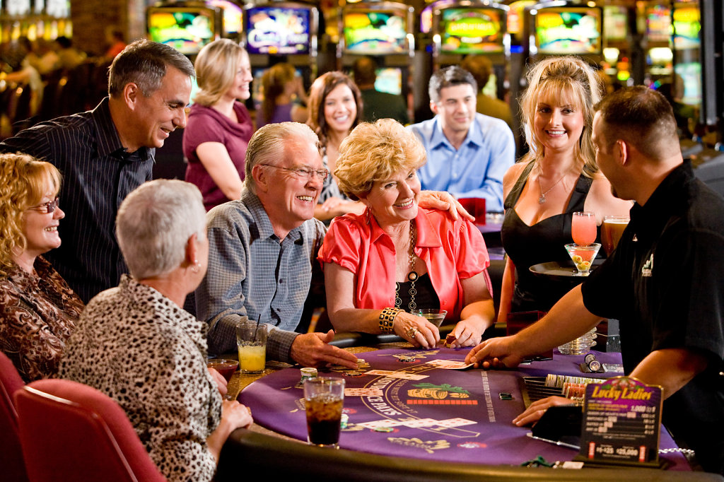 Mature adults playing blackjack at casino