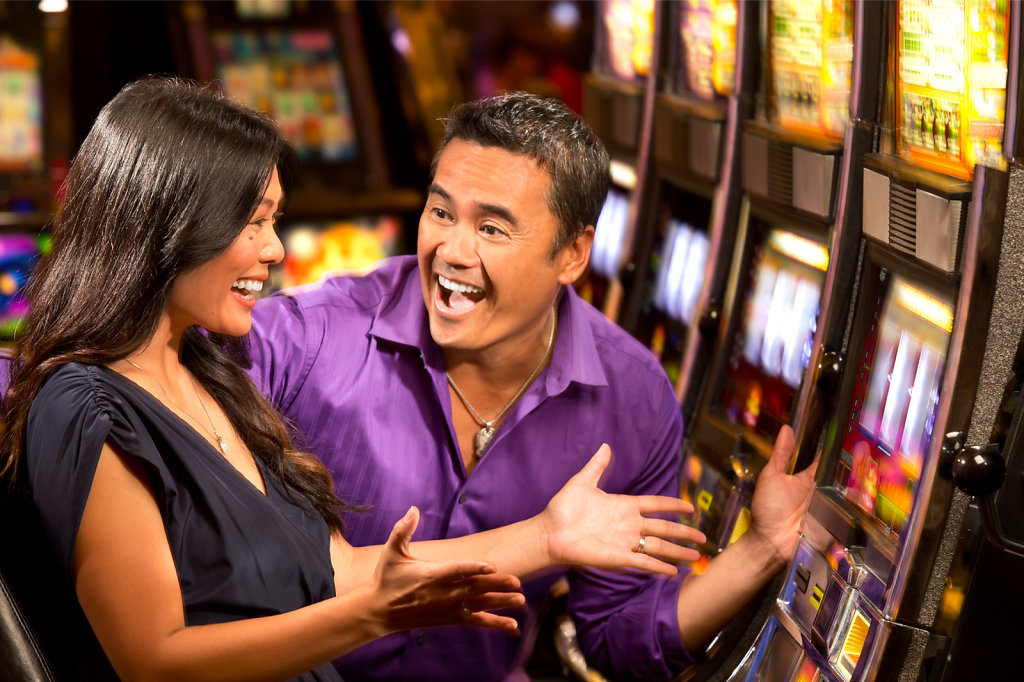 Asian couple celebrate win at casino slots