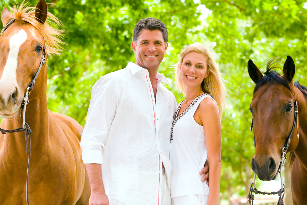 attractive couple dressed in white with riding horses