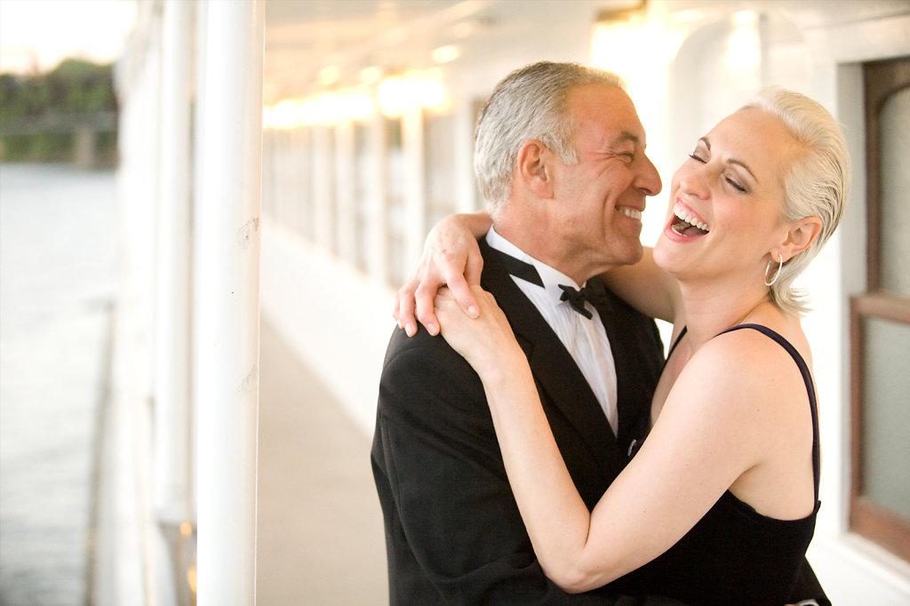 senior couple in tuxedo and black dress dancing and smiling