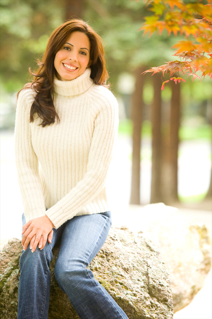 Young lady in wool sweater sitting on rock in nature