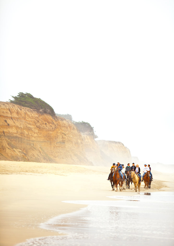 Group of horse riders on beach near cliff