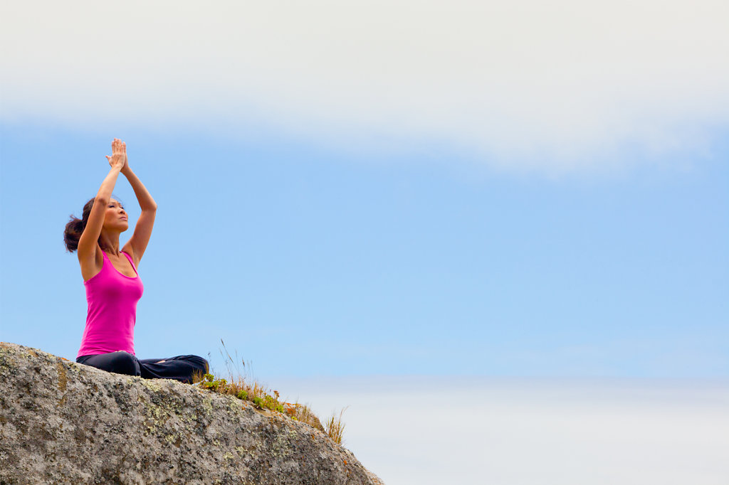 fit woman in yoga pose on rock