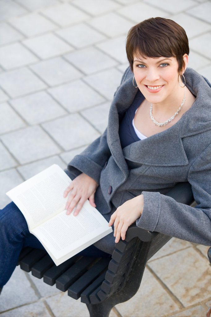 Attractive woman in wool coat reading book on bench