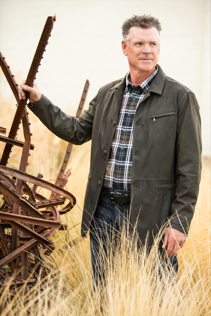 Man in field with rusted steel