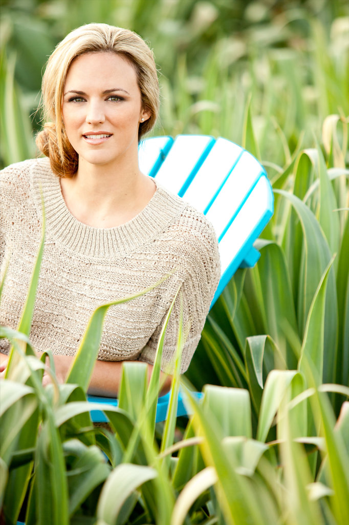 Attractive woman siting in field of big plants sitting in chair summer