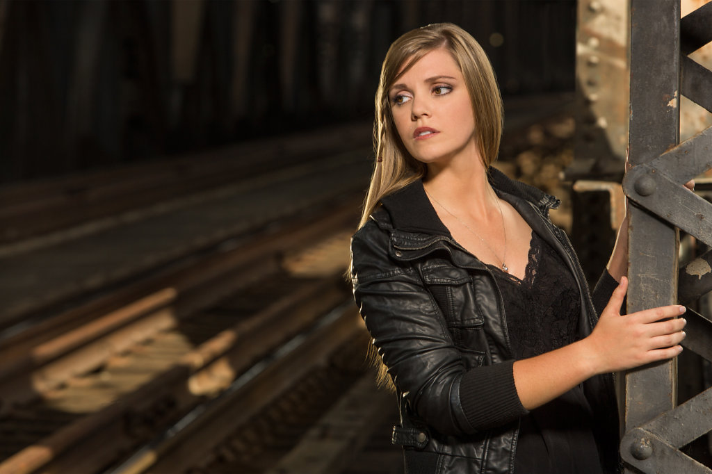 Young lady in black leather jacket near train tracks