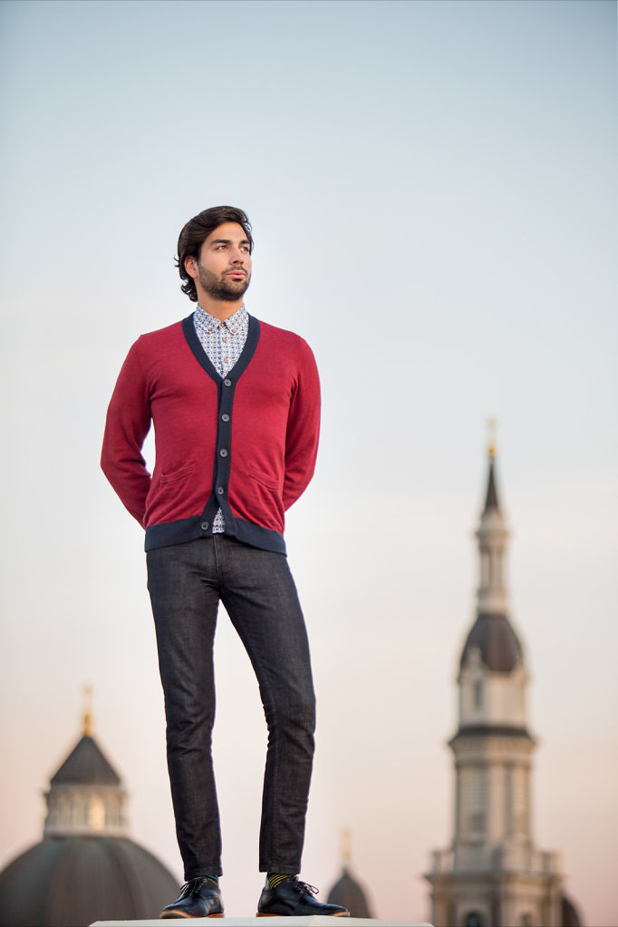Young man in red sweater standing above Sacramento city scape