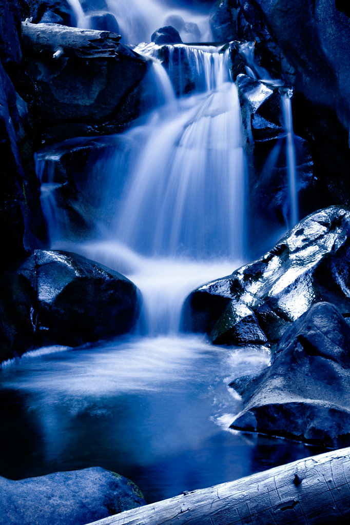 waterfall over big rocks in hues of blue
