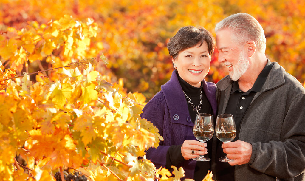 Man and woman sharing wine in fall weather outdoors