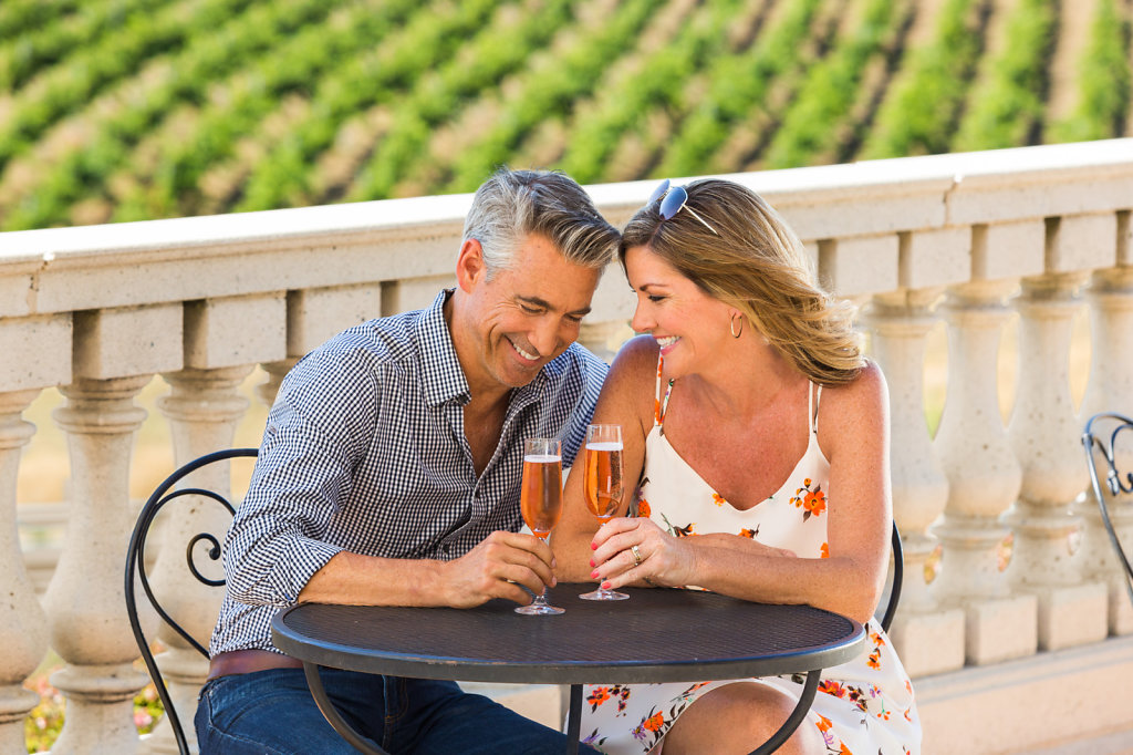 Couple laughing while sharing champagne on veranda