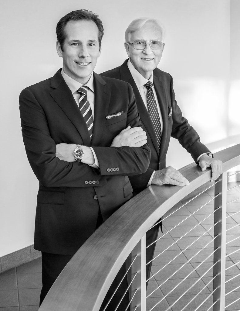 Business portrait of two men in suits at bannister