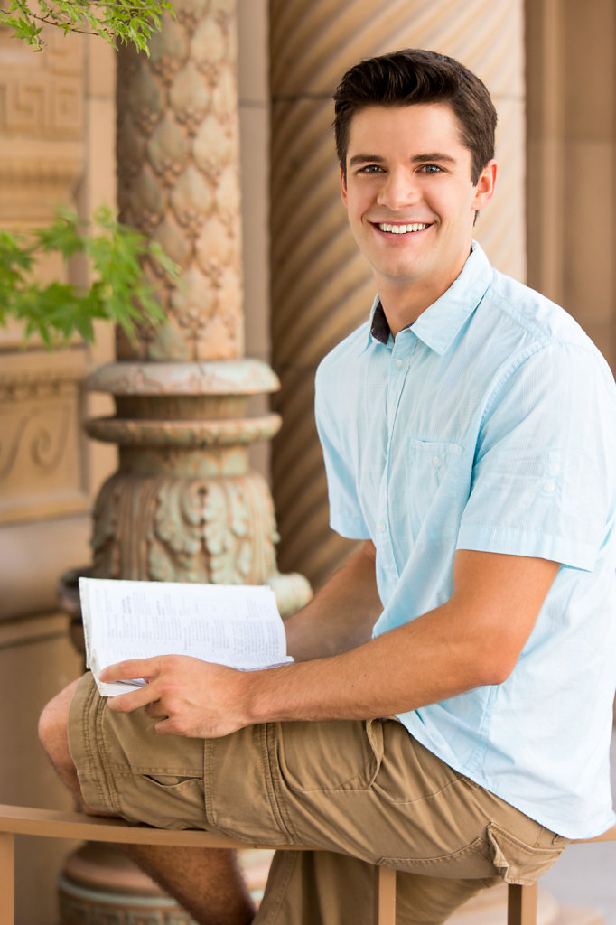 Young man smiling reading a book