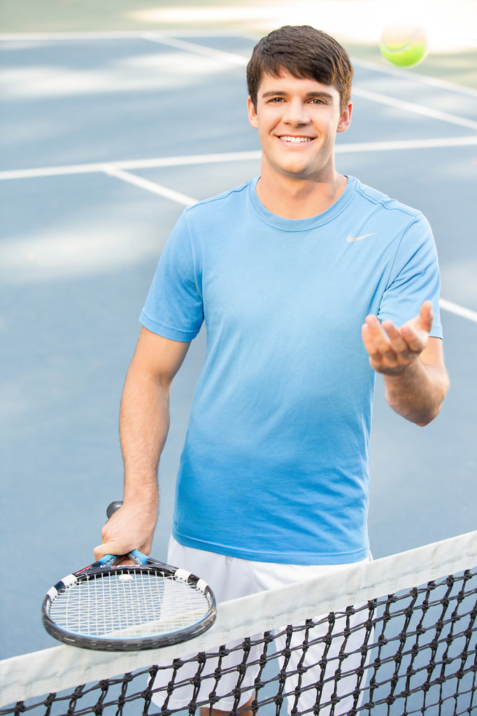 Young man on tennis court with racket and ball in air