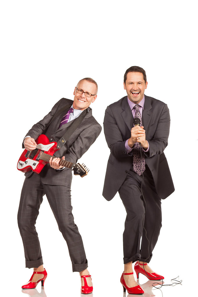 Two men in suits playing instruments in red high heels for benefit