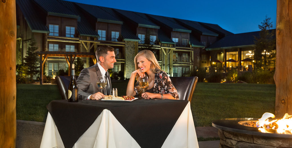 Young couple having dinner and wine at casino restaurant by firepit