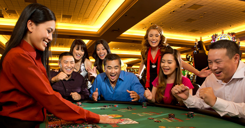 Black Jack Dealer showing hand at group table in casino