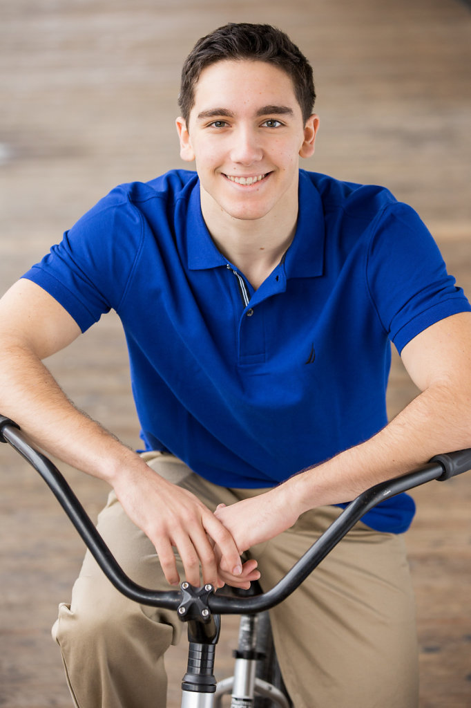 Young man on cruiser bike smiling