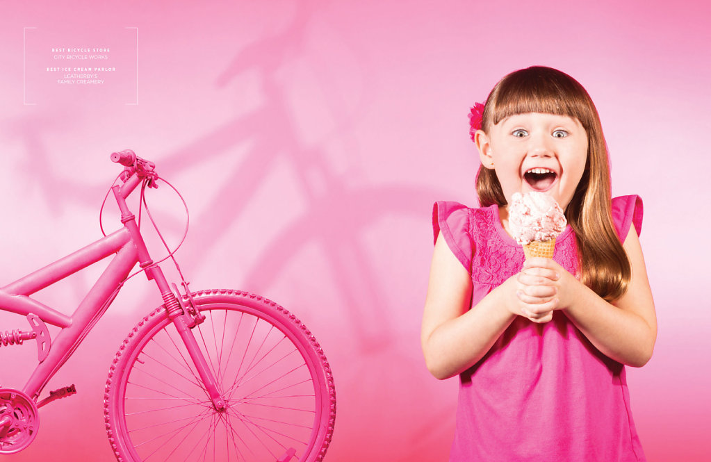 Young girl with ice cream next to pink mountain bike