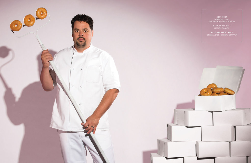 Chef holding donuts next to boxes of donuts