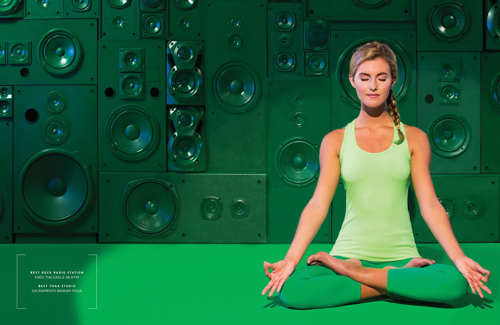 Young lady in green outfit doing yoga in front of green speakers