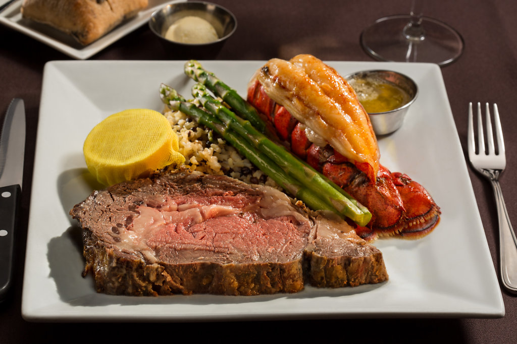 rime rib with baked lobster, wild rice and asparagus on white platter