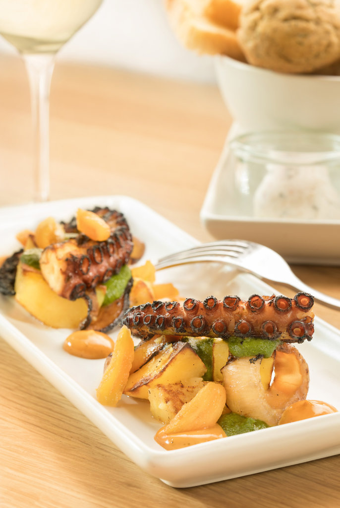 Grilled Tako Octopus over sauted garlic and celery on white platter