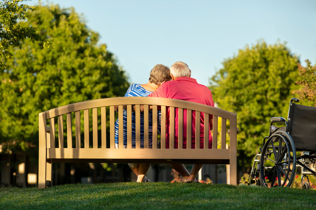 Old couple sitting on bench in park next to wheelchair