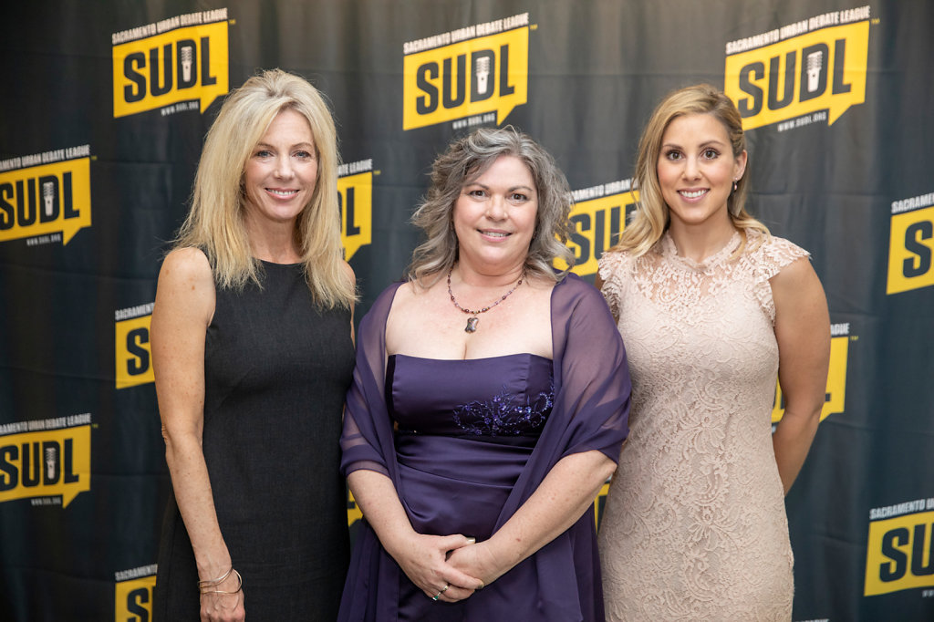 Three women in cocktail dresses speakers event