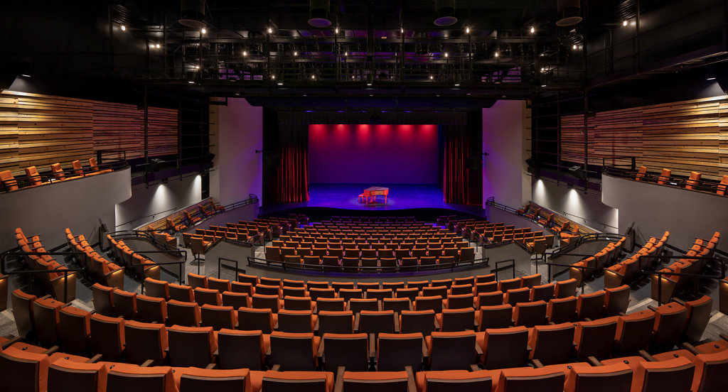 Panoramic wide angle shot of theater with piano on stage