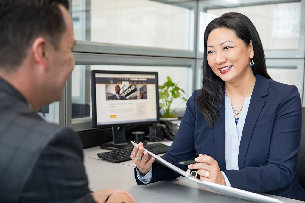 Asian Woman Talking to Client at Desk