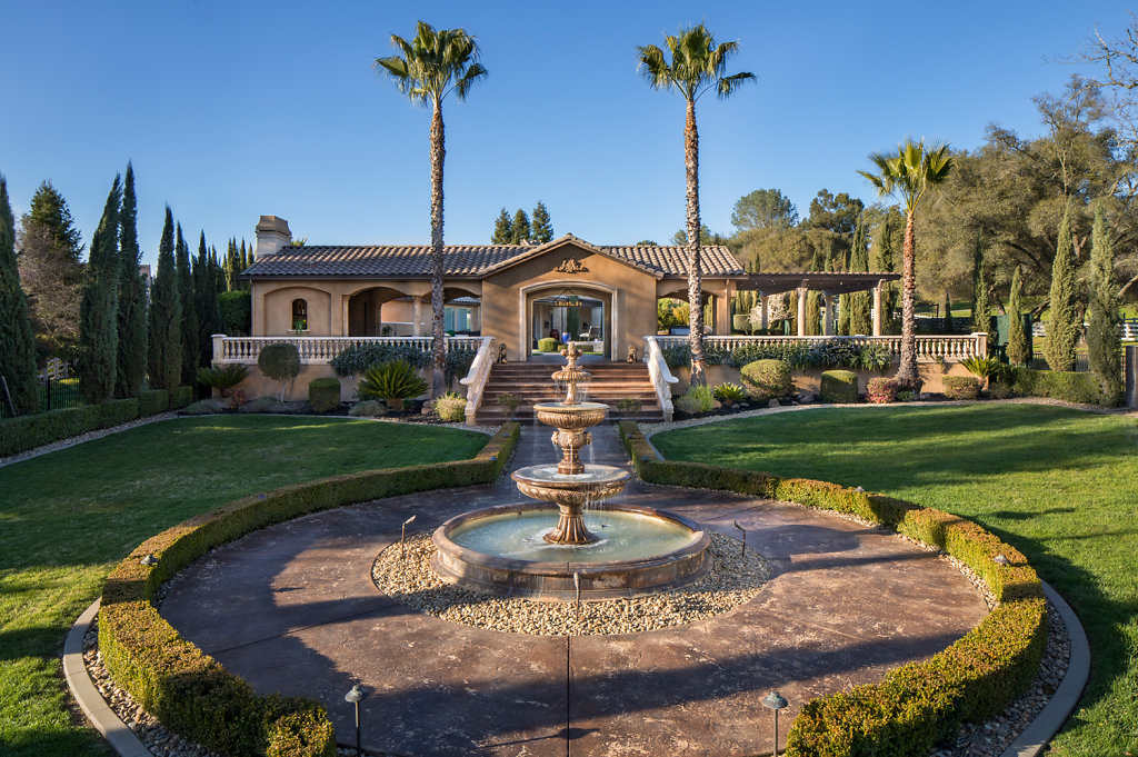 Big backyard with fountain and palm trees