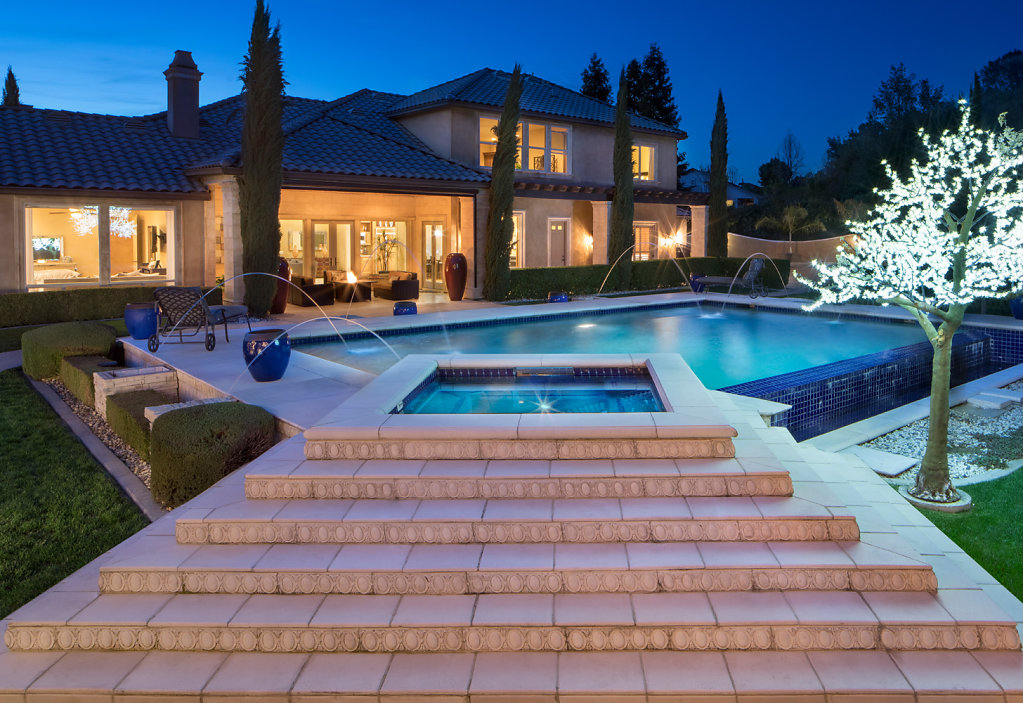 Big backyard at twilight with infinity pool and fountains